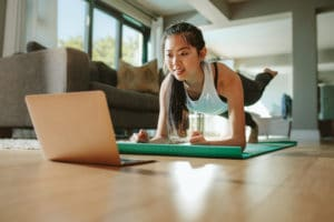 Woman working out at home watching video tutorial on laptop. Fit young woman in plank position repeating online instructions by coach on computer.