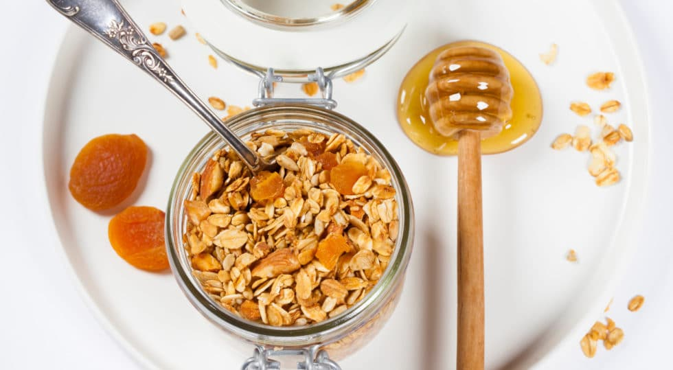 Homemade granola (with dried fruit and nuts) and healthy breakfast ingredients - honey, milk and fruits on white background