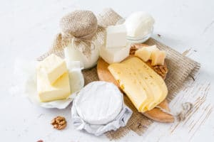 Selection of milk and dairy products on white wood background
