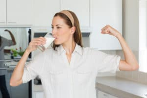 Young woman flexing muscles while drinking milk in the kitchen at home