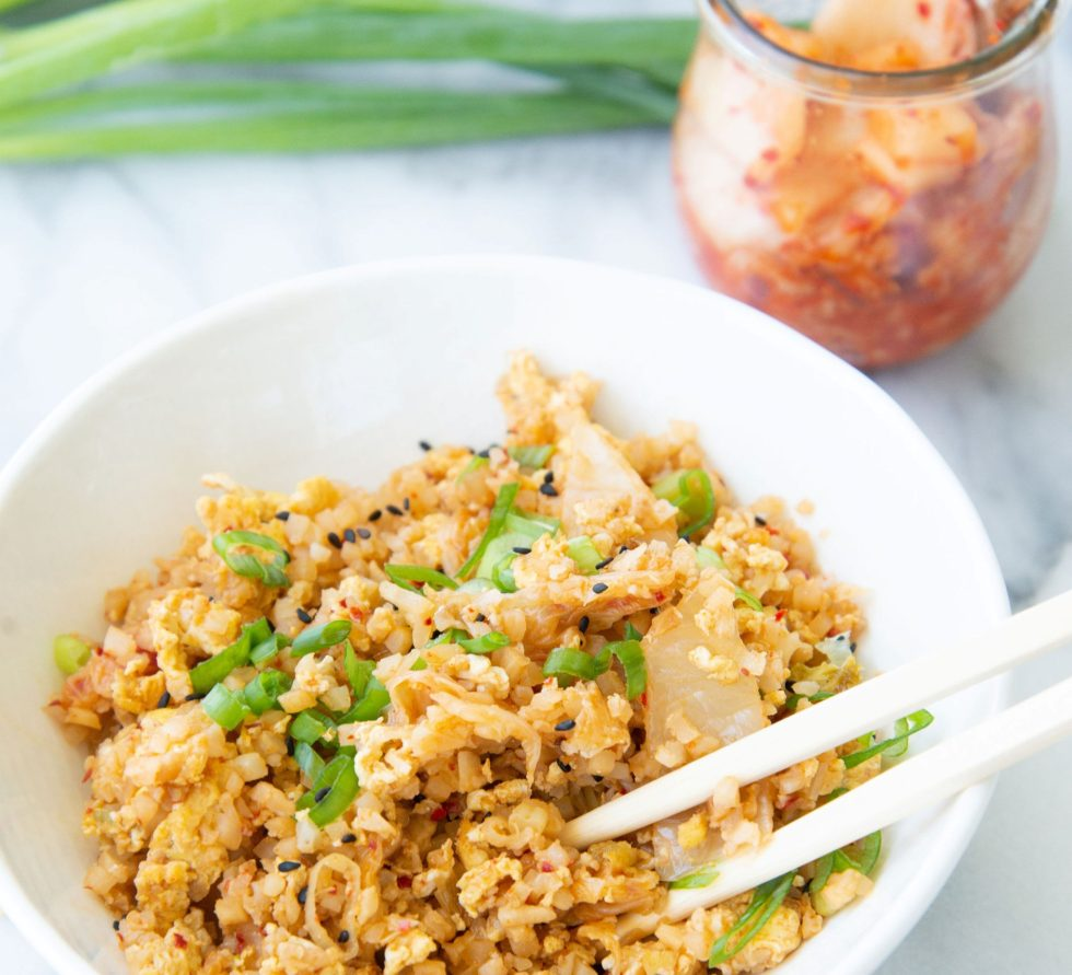 Kimchi fried cauliflower rice in a bowl with a side of kimchi on the side.