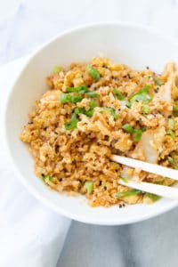 Kimchi fried cauliflower rice in a bowl with chopsticks.
