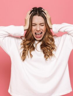 Portrait of an irritated young casual girl screaming isolated over pink background
