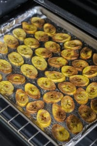 Cooked plantain chips on baking sheet