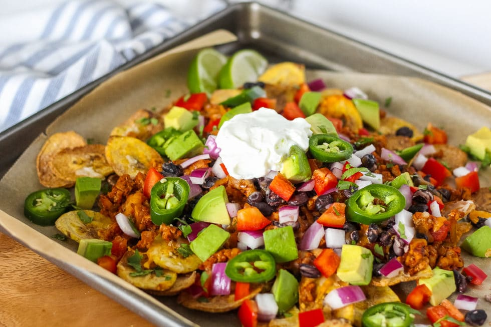 Side view of loaded plantain nachos on baking sheet