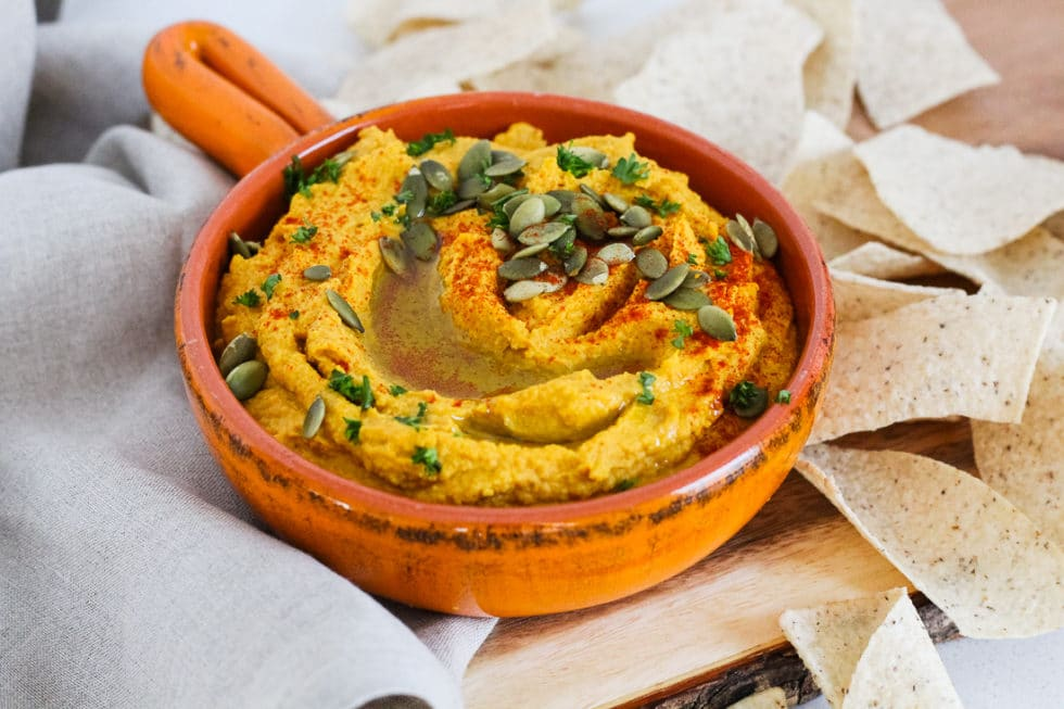 Savory pumpkin hummus in bowl, side view with tortilla chips around it.