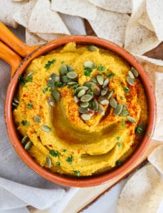 Savory pumpkin hummus in bowl with tortilla chips around it. View from above.
