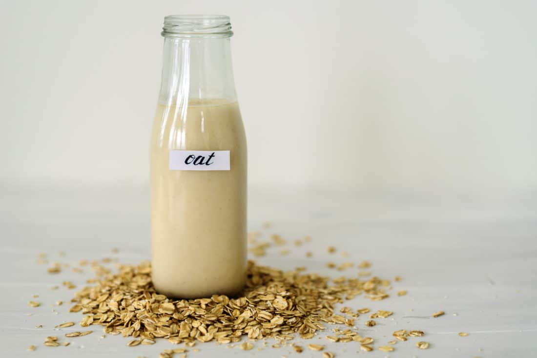 Glass bottle of oat milk on white background behing heap of oatmeal flakes