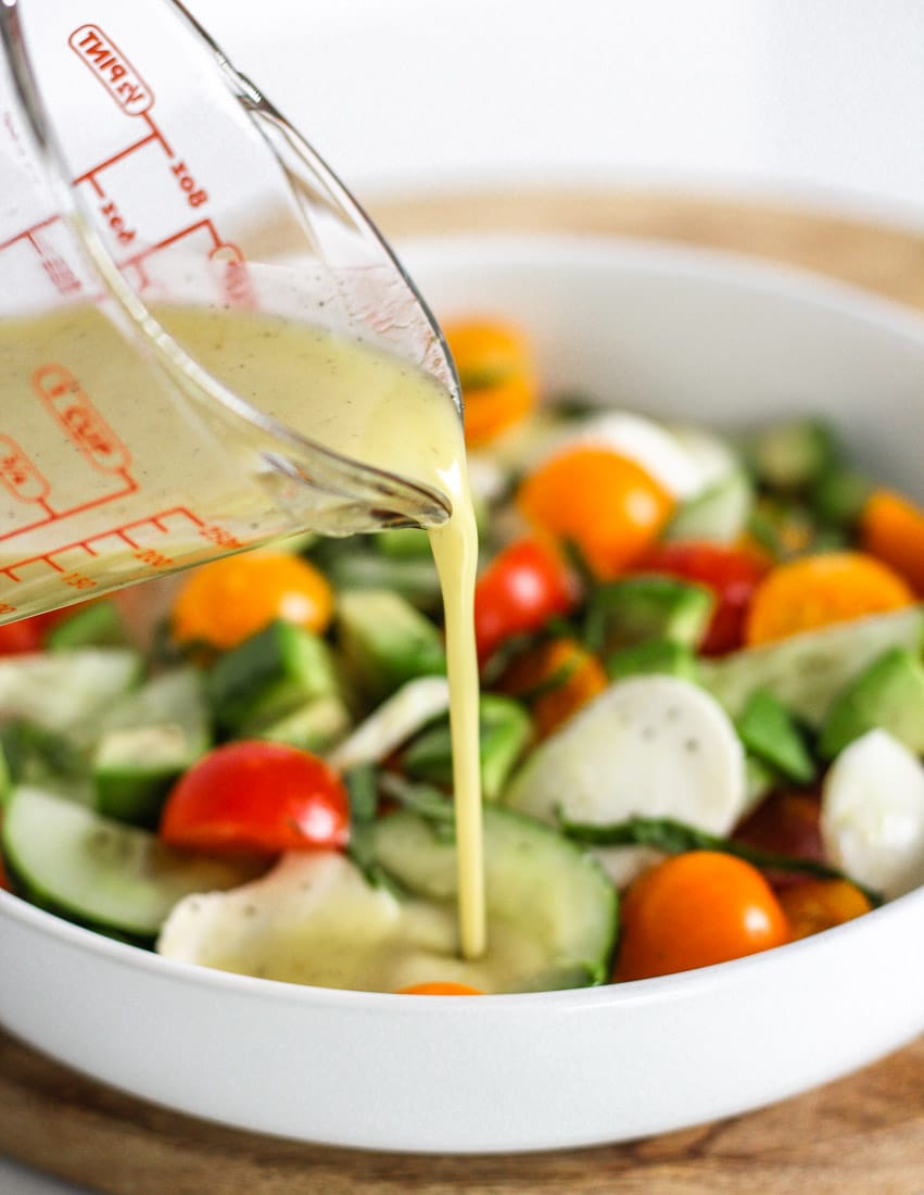 apple cider vinaigrette dressing being poured onto a bowl of salad.