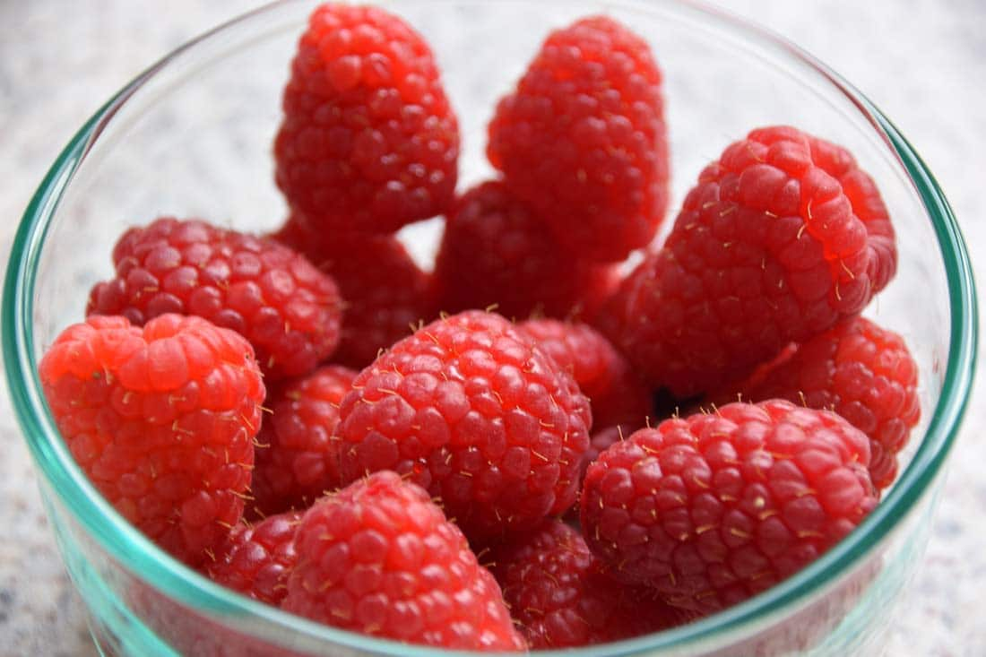 small glass bowl filled with fresh raspberries