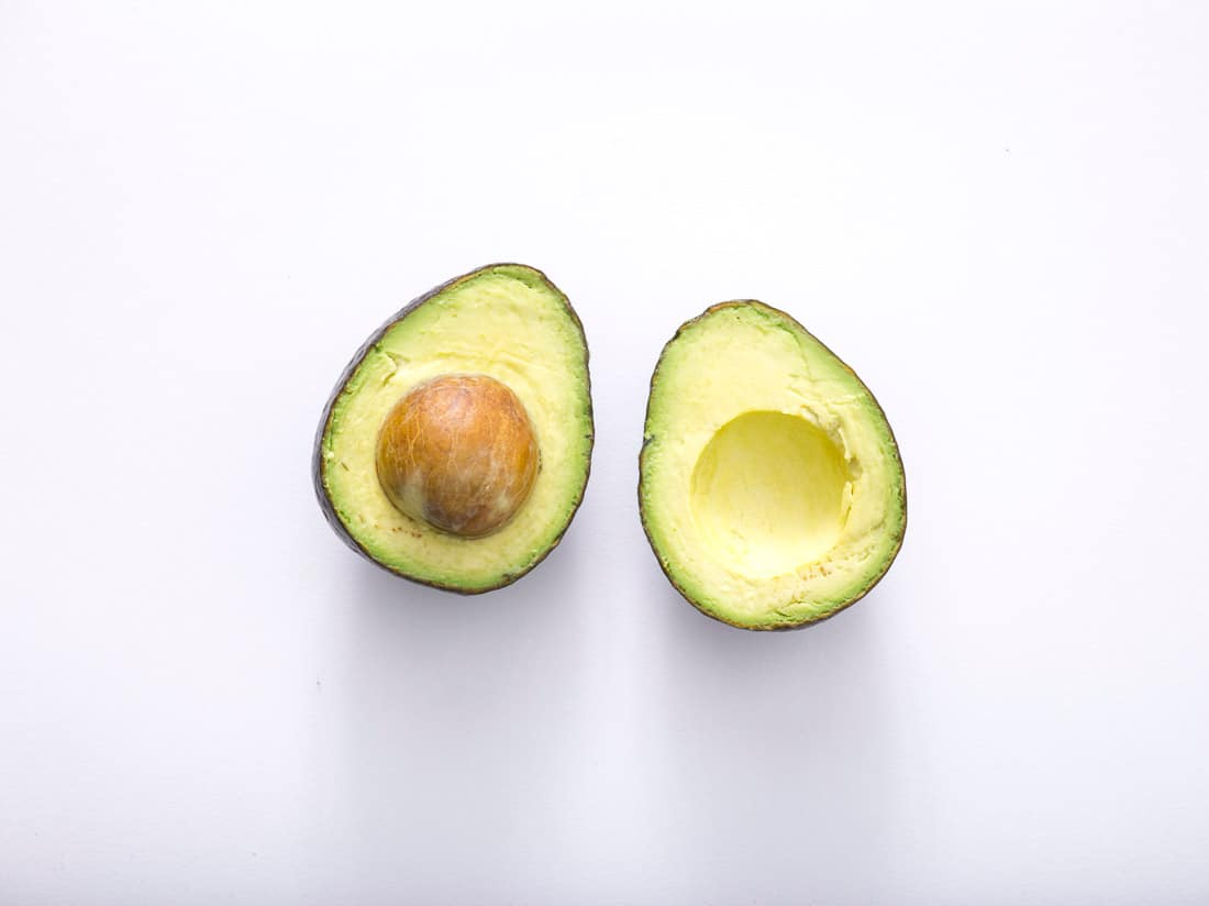 avocado sliced in half on white background