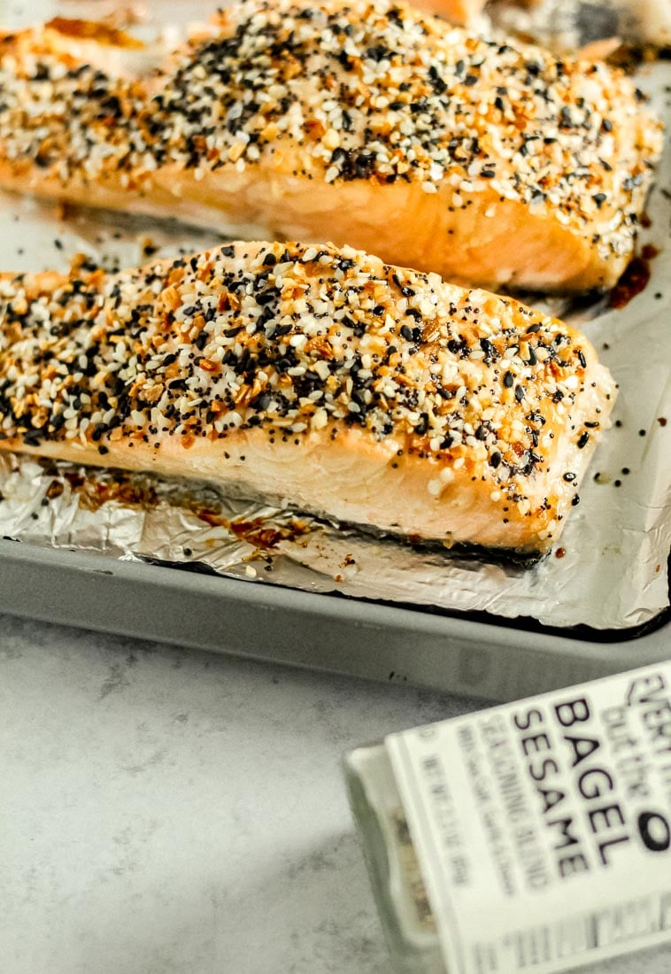 Everything bagel salmon on a foil-lined baking sheet with everything bagel seasoning next to it.