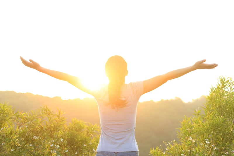 woman standing in the sun with arms wide open