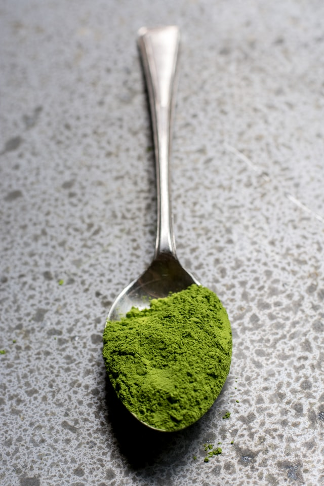 Spoonful of Athletic Greens powder on a marble counter top