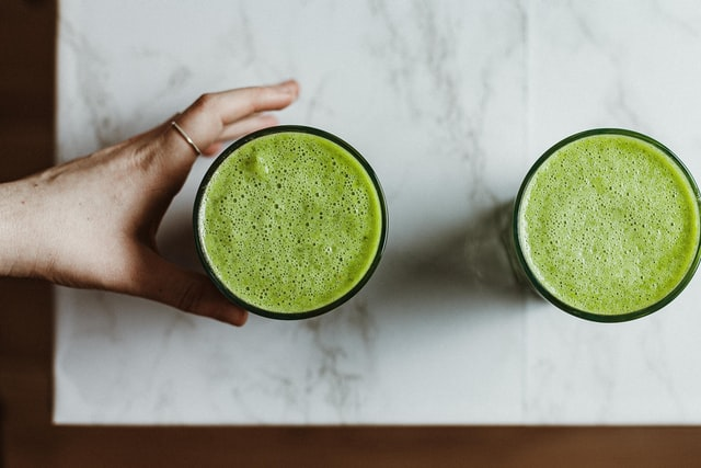 A woman reaching for a glass of Athletic Greens that is sitting on a marble counter