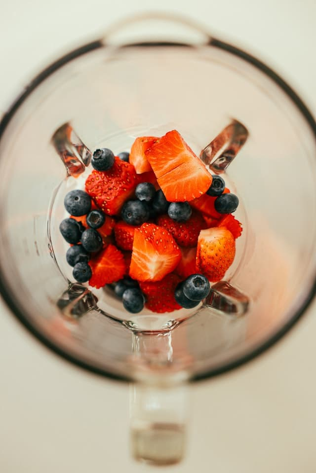 Overhead view of inside blender with strawberries and blueberries inside it.