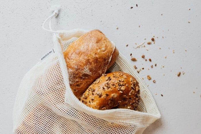 Fresh bread loaves in a reusable produce bag.