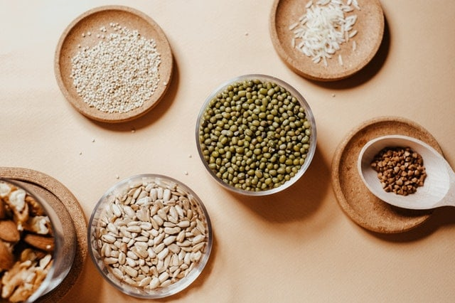 Overhead view of grains, seeds, nuts, and peas in small wooden and glass bowls.